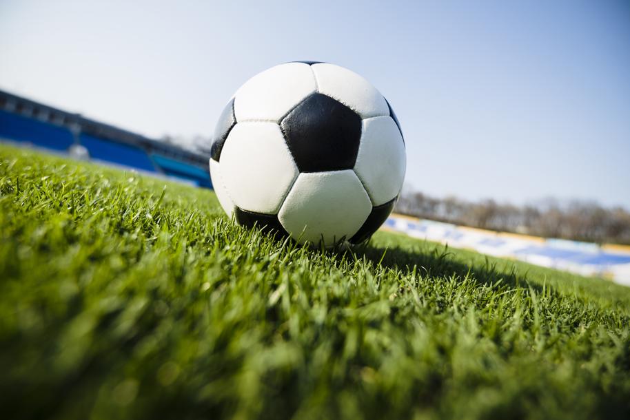 Balón de fútbol en cancha sintética Icaza-Ortiz Abogados